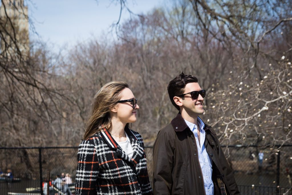 Man and woman wearing sunglasses walking in Central Park for article on Central Park Lake proposal tips