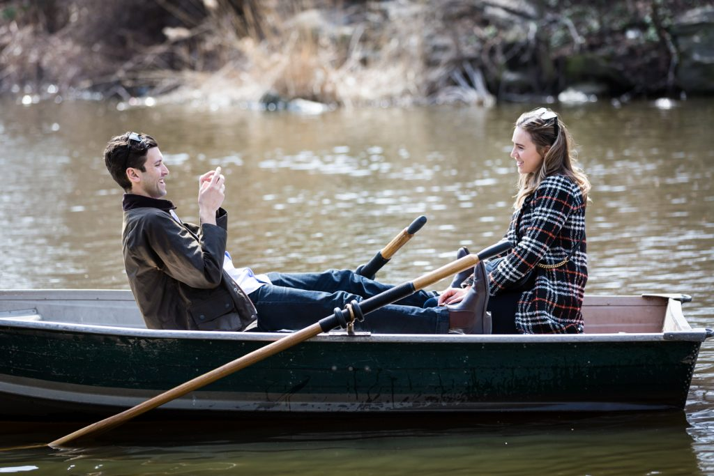 Man in boat taking photo of girlfriend with cell phone