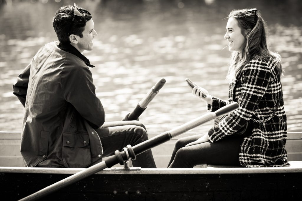 Black and white photo of man in boat asking his girlfriend to marry him