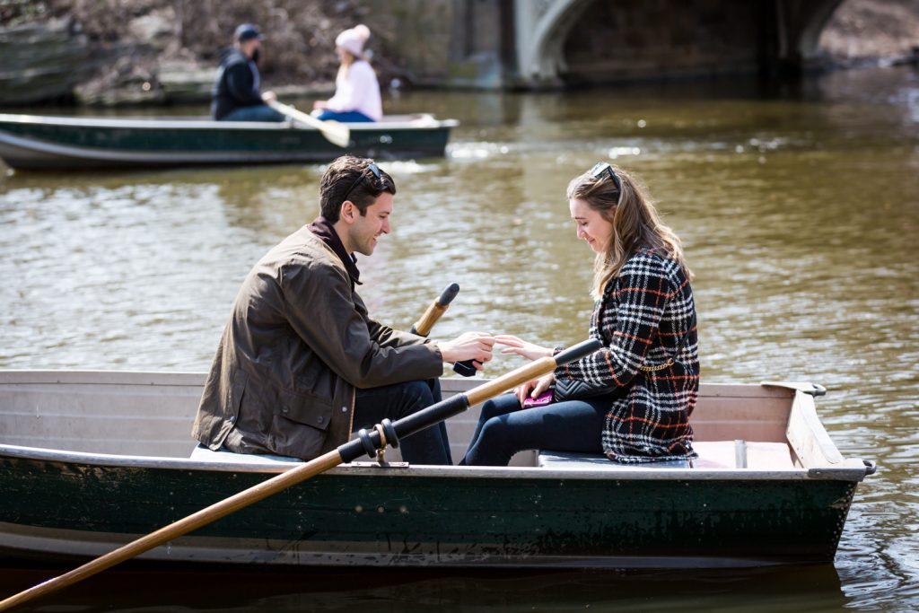 Man in at putting ring on woman's finger for article on Central Park Lake proposal tips