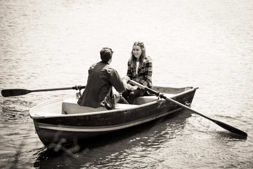 Black and white photo of man and woman in boat