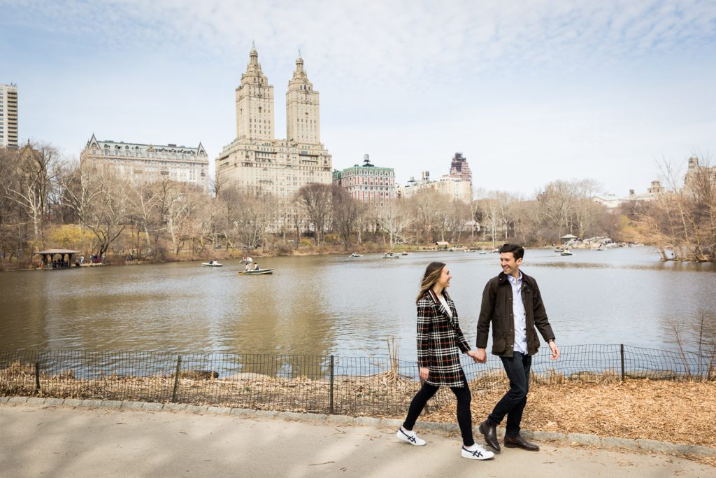Man and woman walking hand-in-hand past Central Park Lake for an article on Central Park Lake proposal tips