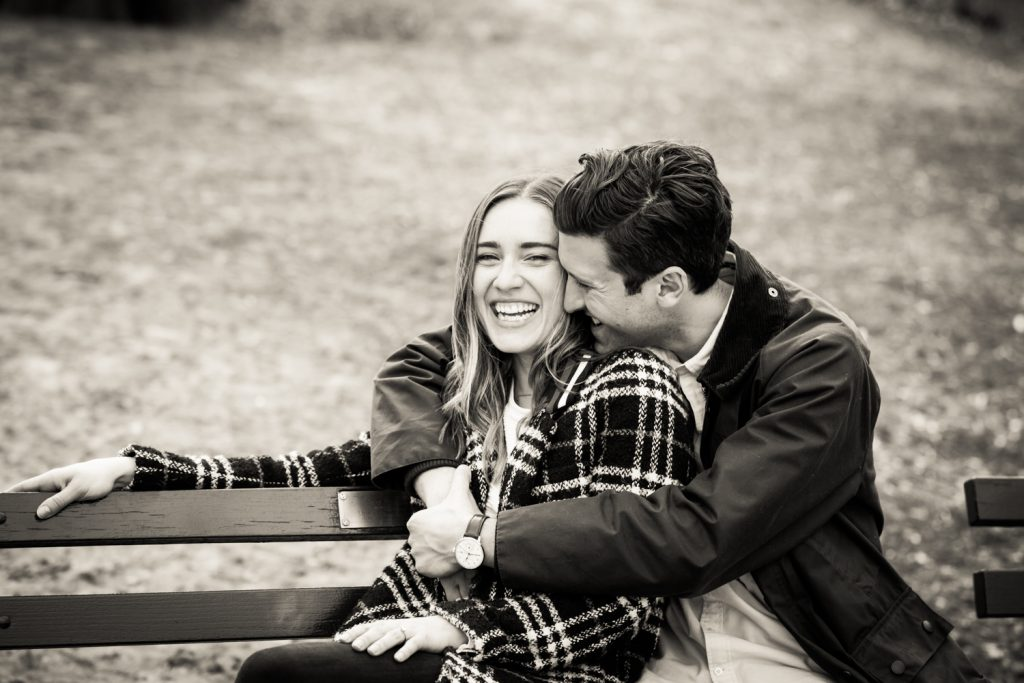 Black and white portrait of couple hugging on bench