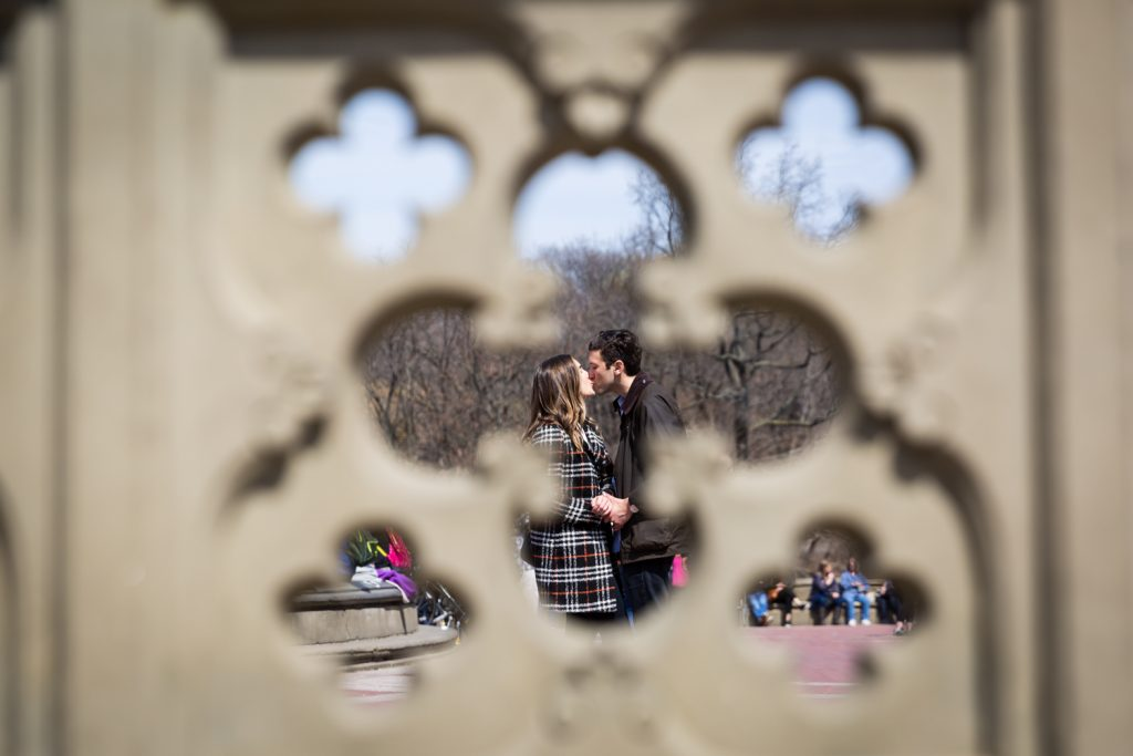View of couple kissing through fence in Bethesda Fountain