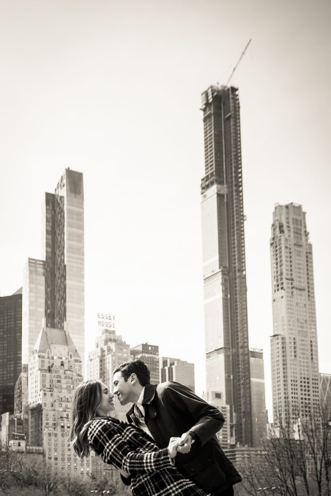 Black and white photo of man dipping woman with NYC skyline in background