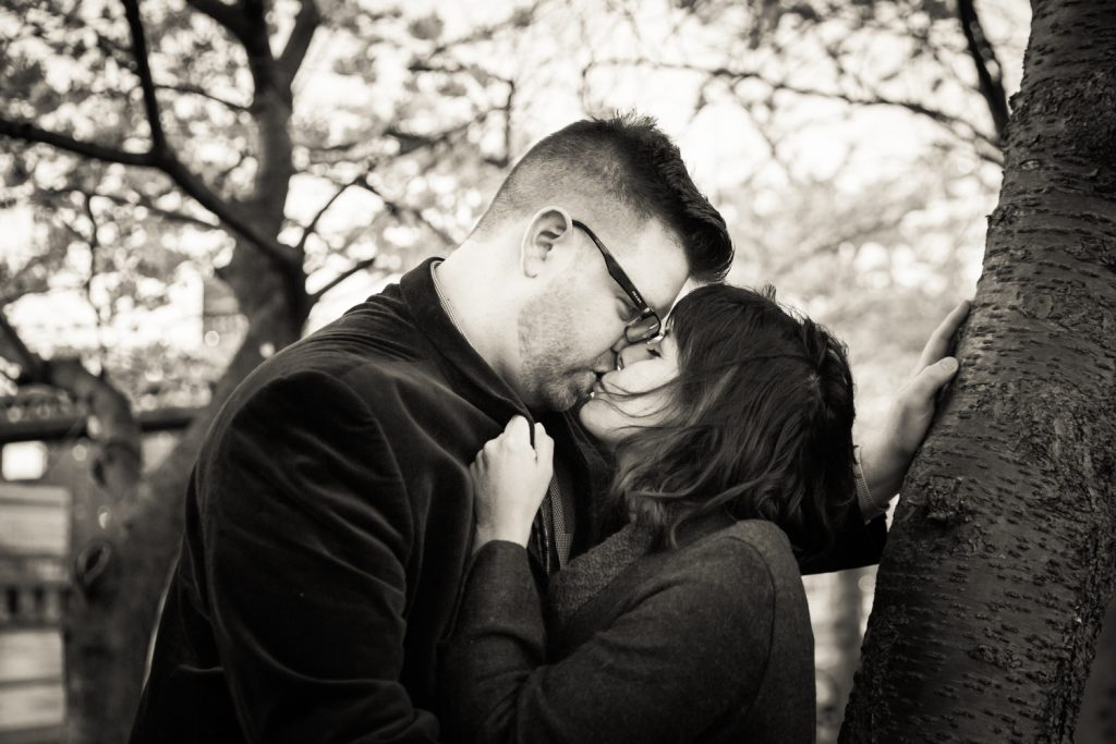 Black and white photo of couple kissing underneath cherry blossom trees