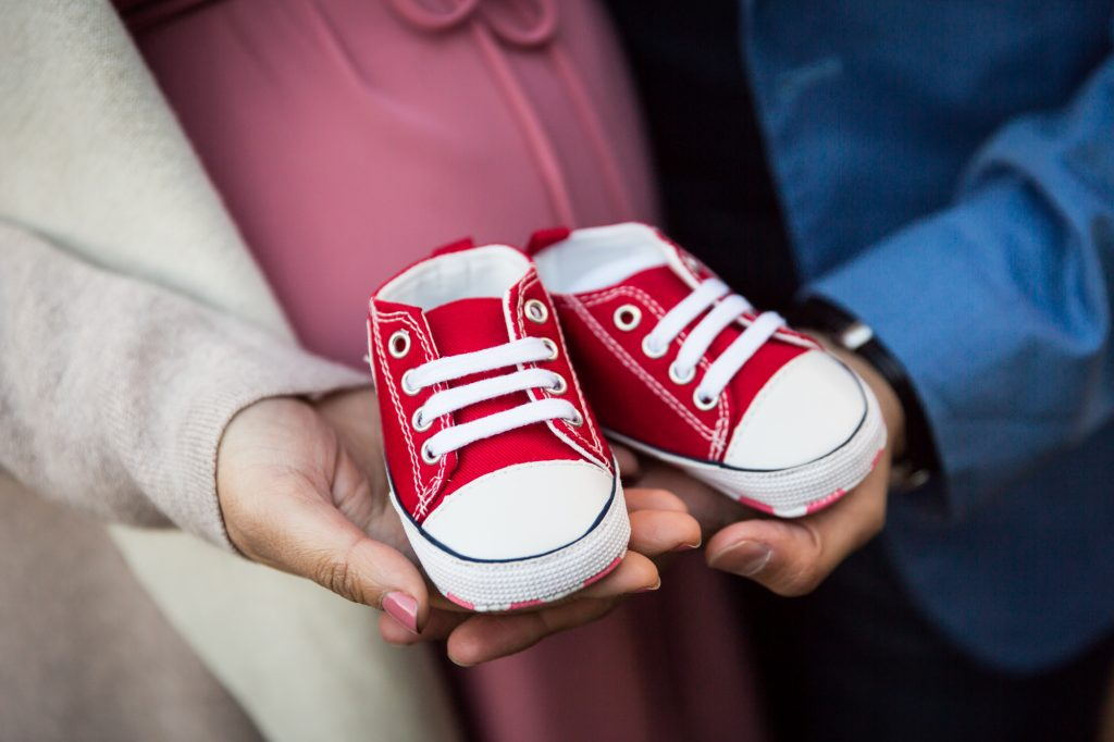 Hands holding baby shoes for an article on maternity portrait tips