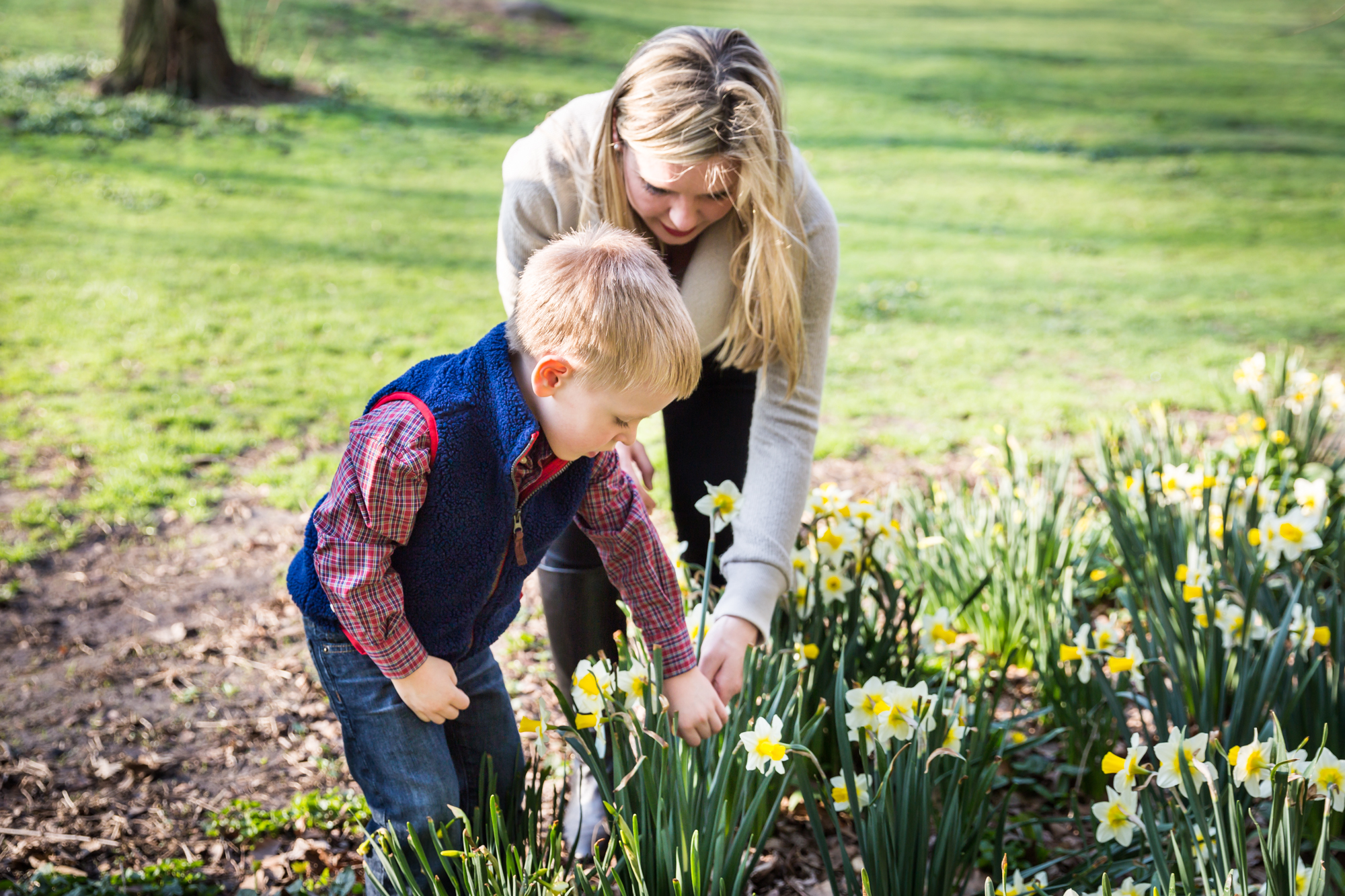 Mother and child picking daffodils for an article on the best family portrait poses