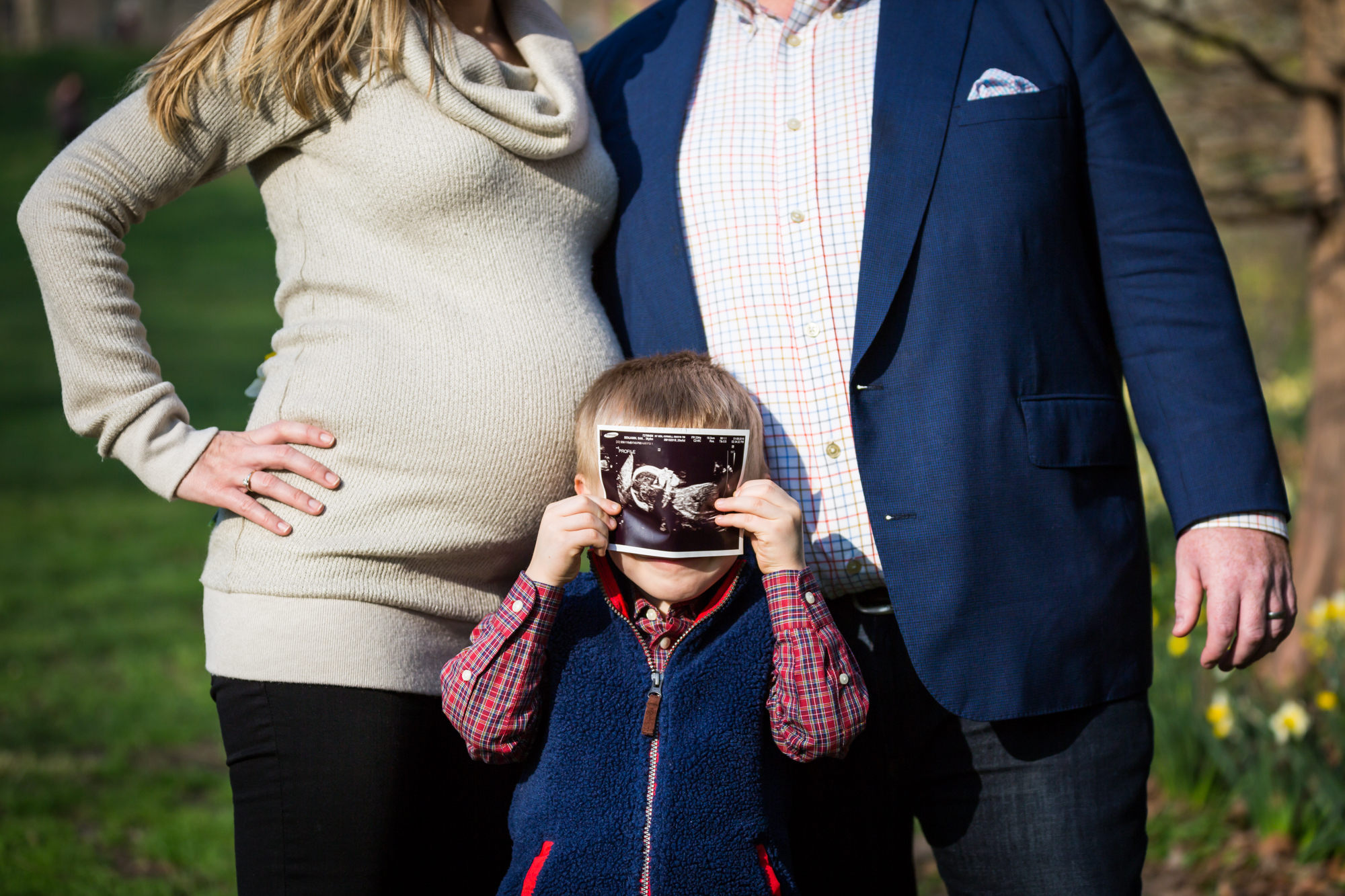 Family with child with sonogram photo for an article on the best family portrait poses