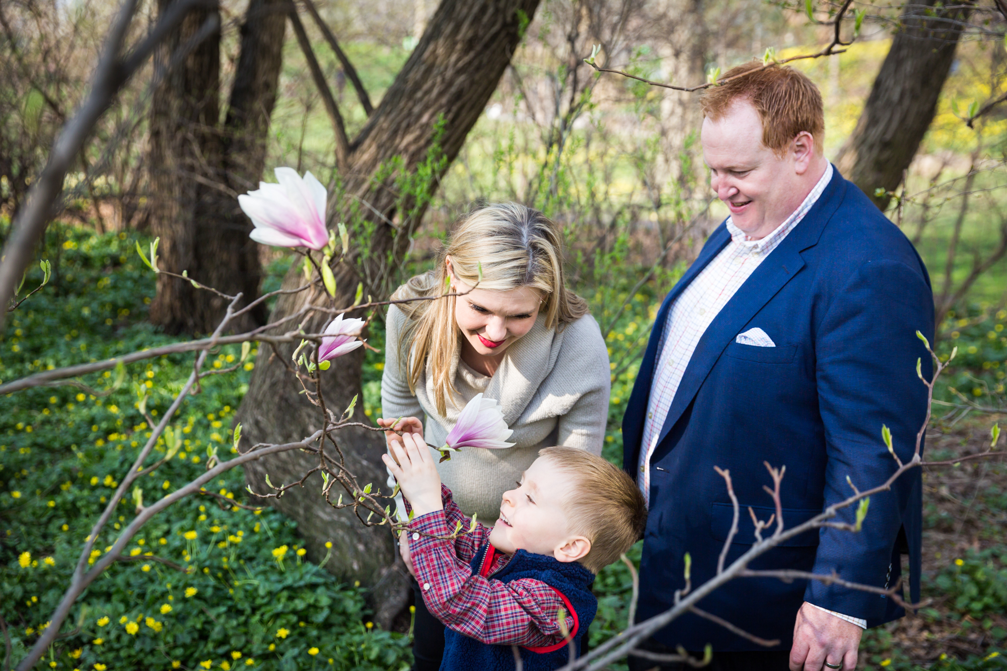 Parents and child smelling flower for an article on the best family portrait poses