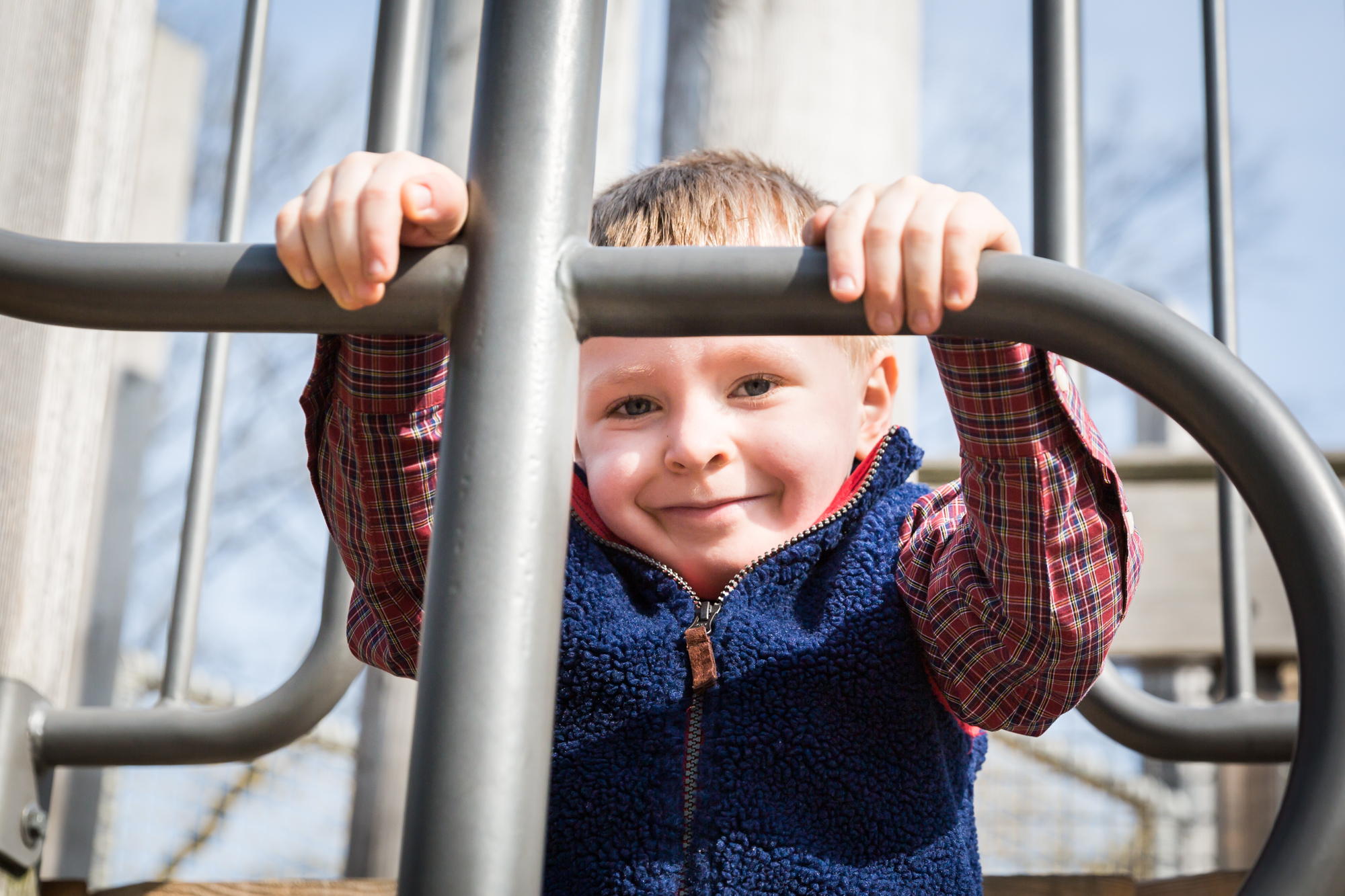Child on playground equipment for an article on the best family portrait poses