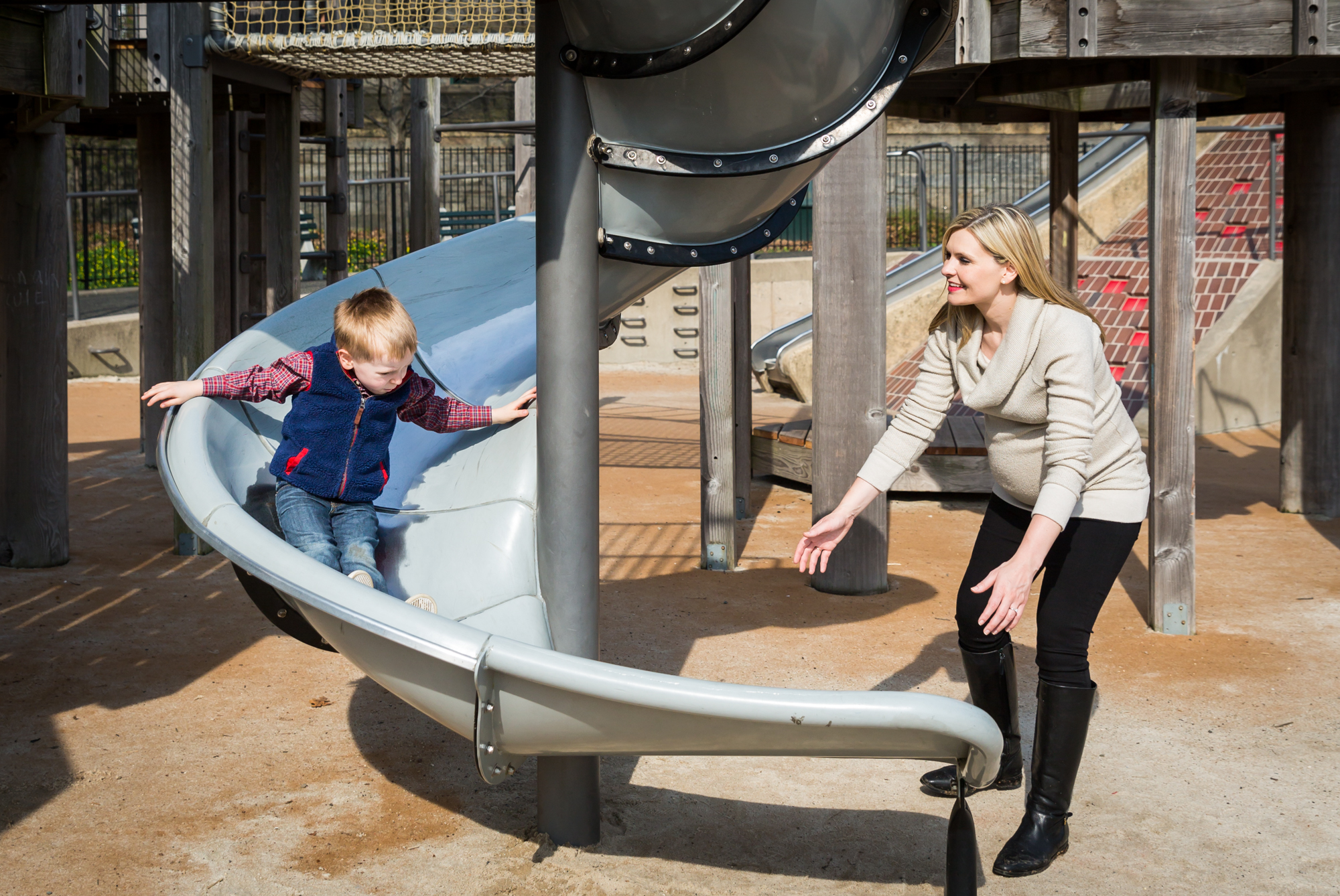 Mother with son going down slide for an article on the best family portrait poses