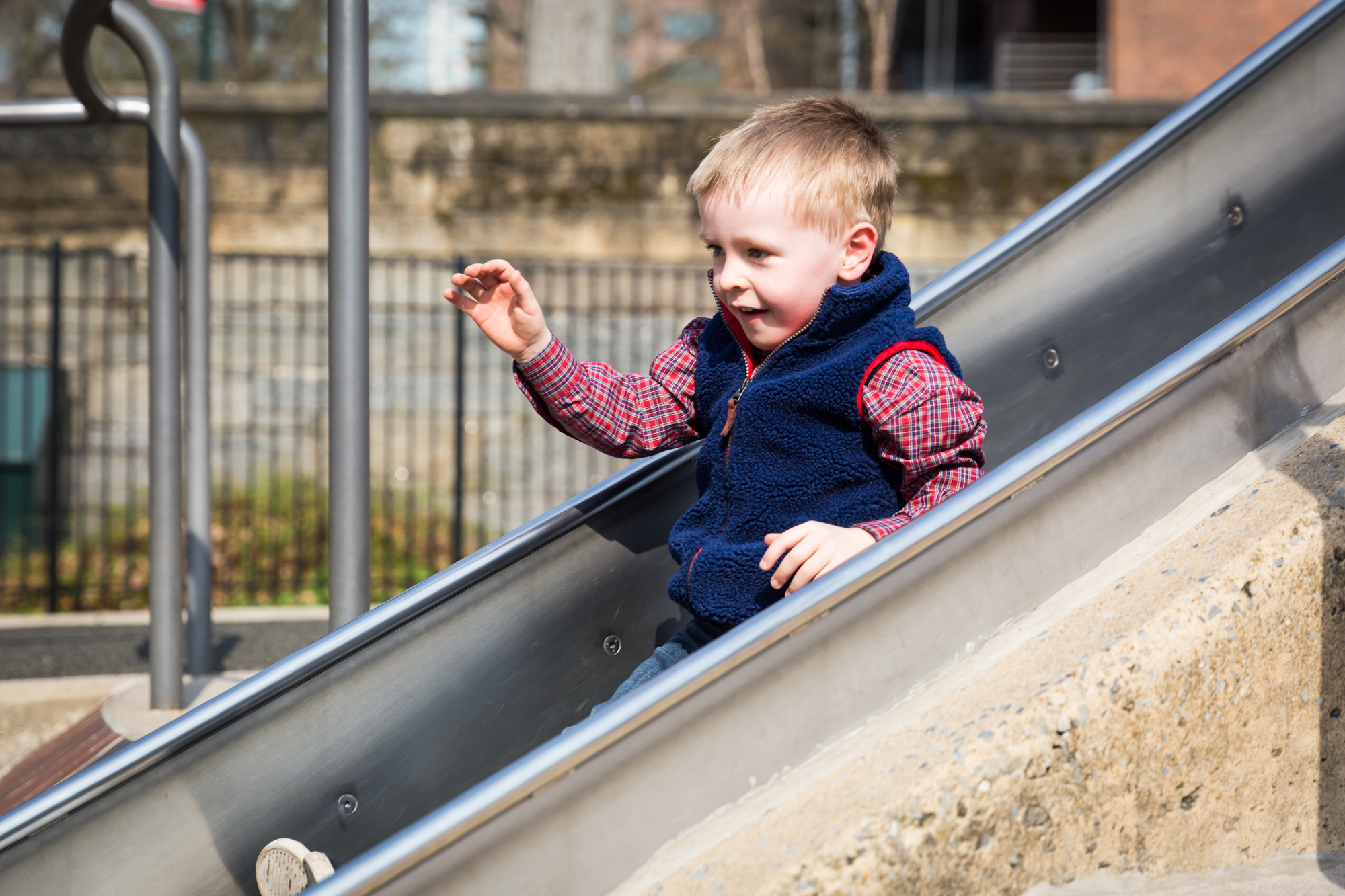 Little boy on slide for an article on the best family portrait poses