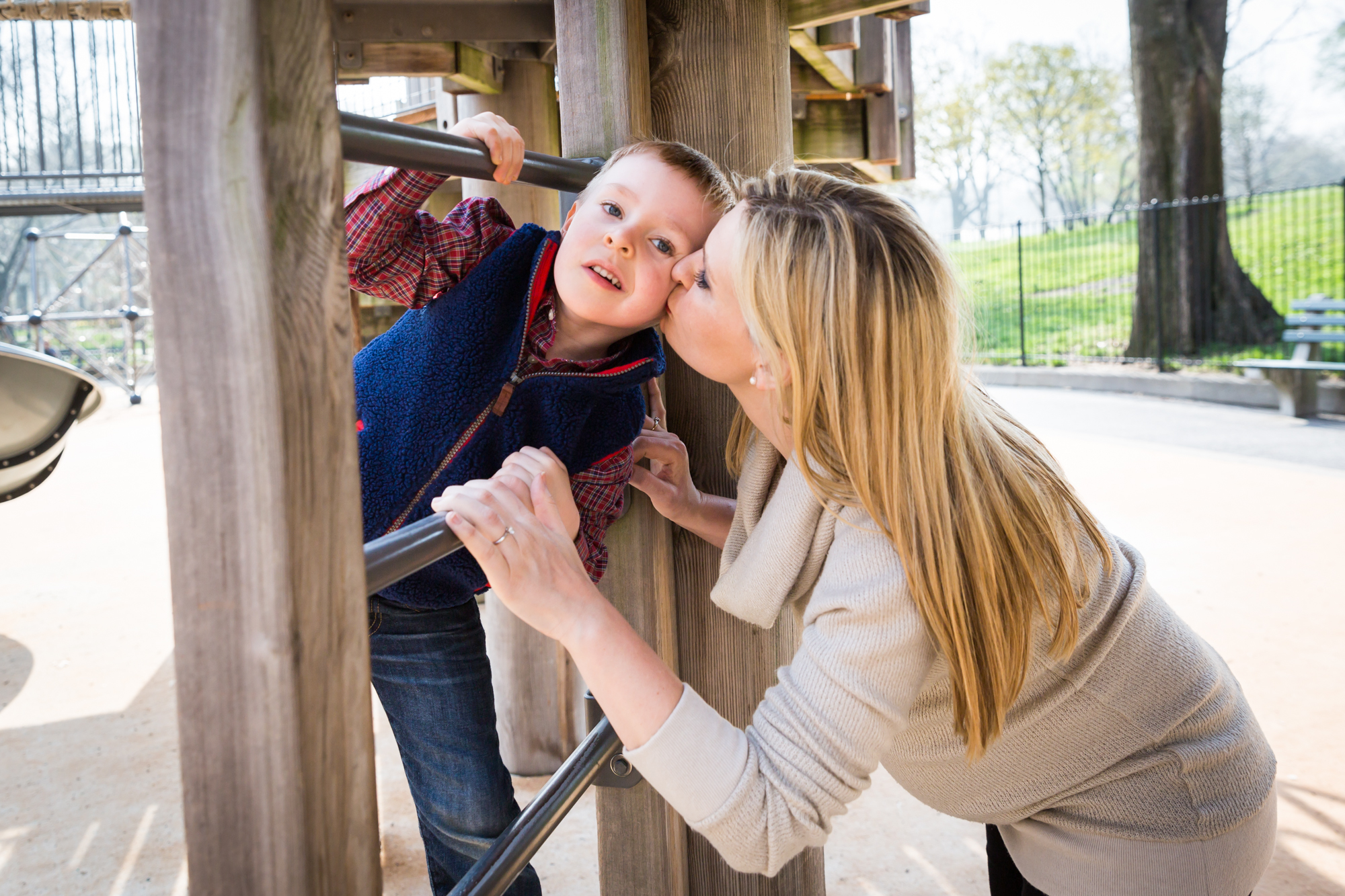 Mother kissing son on playground for an article on the best family portrait poses
