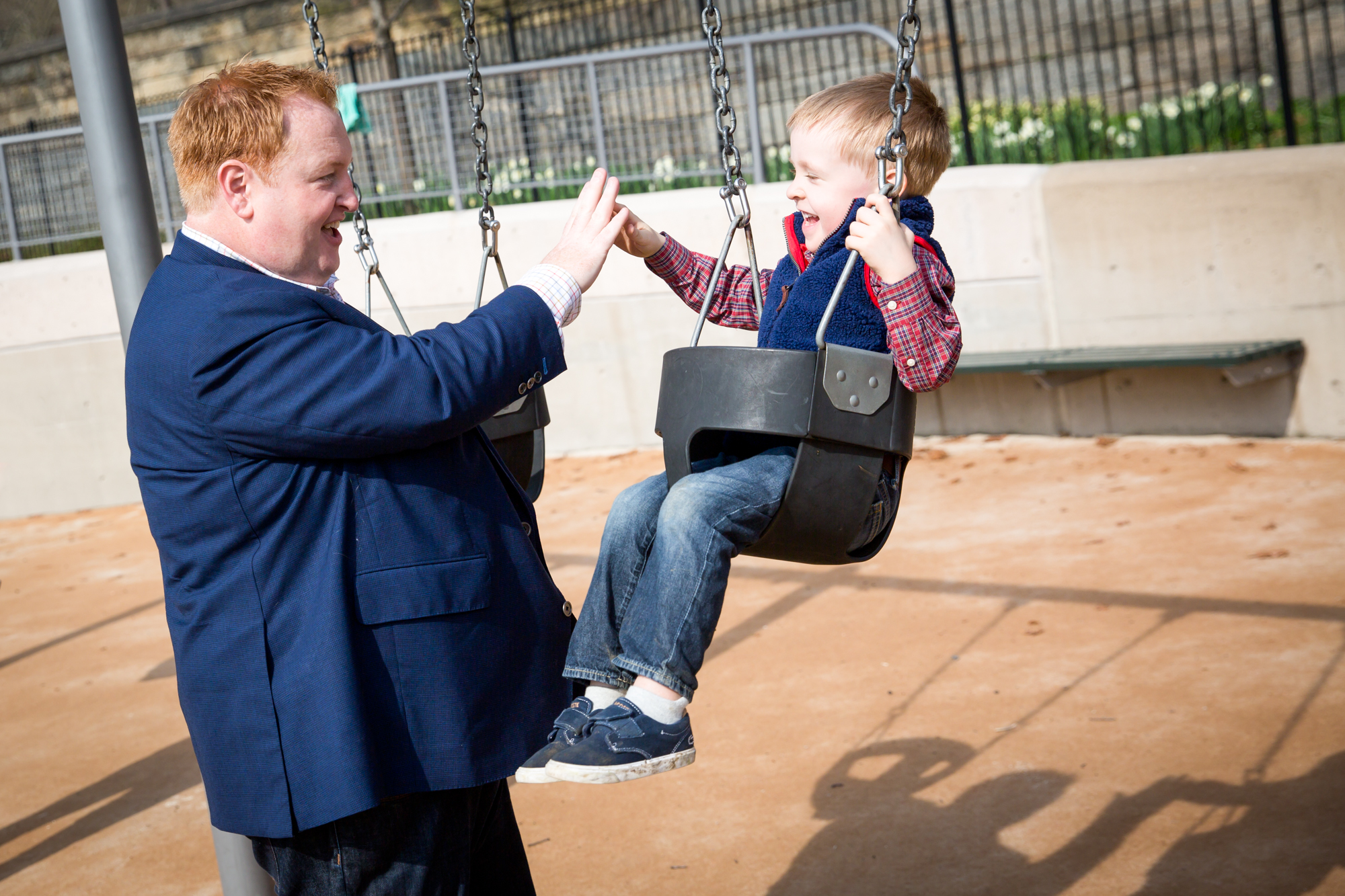 Father with son on swing for an article on the best family portrait poses