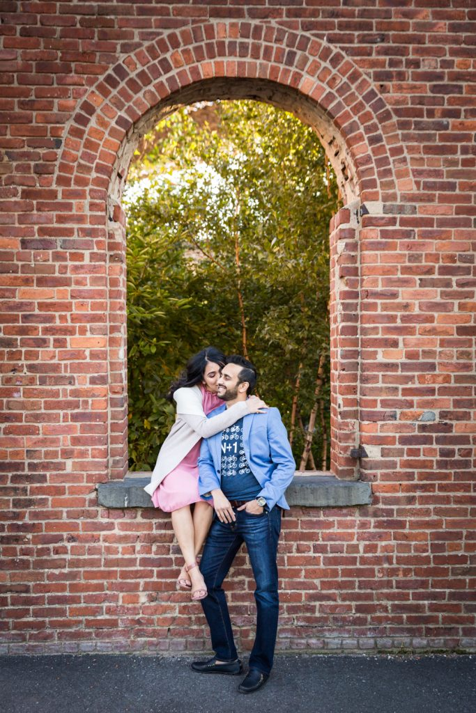 Pregnant woman kissing her husband's cheek in brick archway for article on maternity portrait tips
