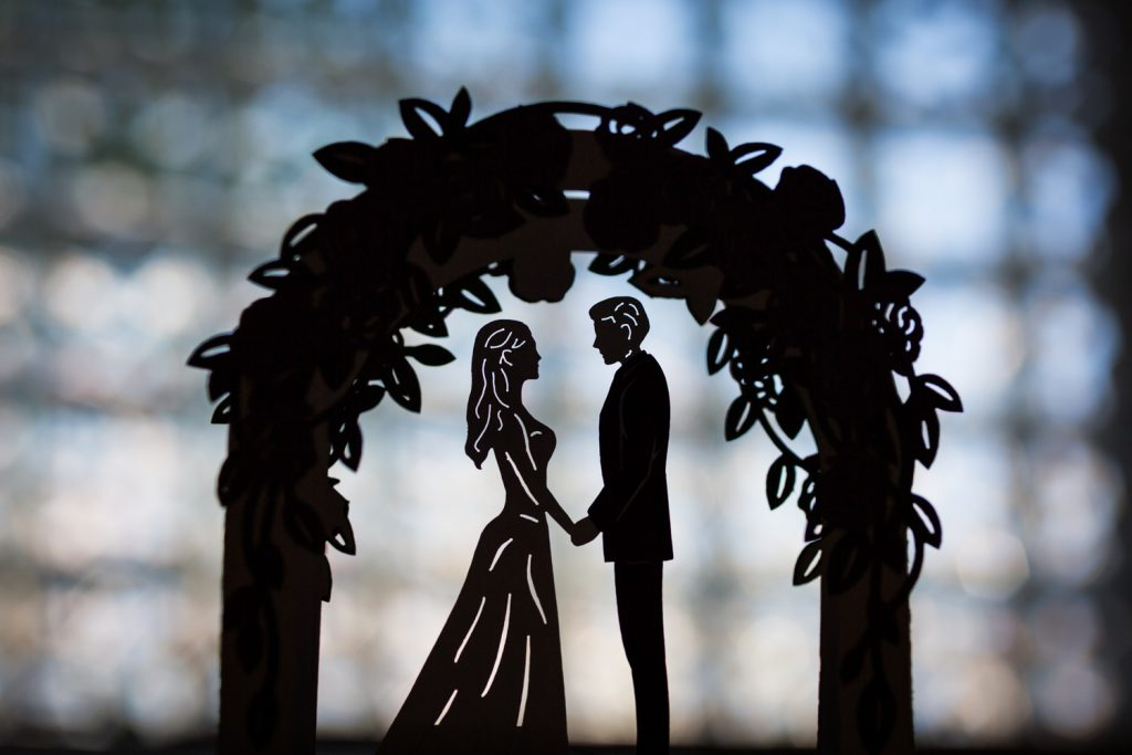 Backlit wedding cake topper of bride and groom under arch