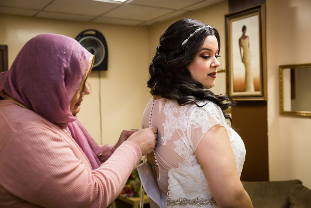 Mother of the bride buttoning bride's dress for an article on wedding photography timeline tips