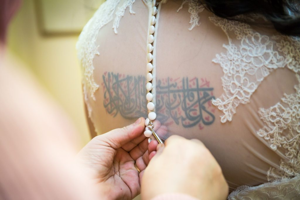 Close up of hands buttoning wedding dress on bride with Arabic back tattoo