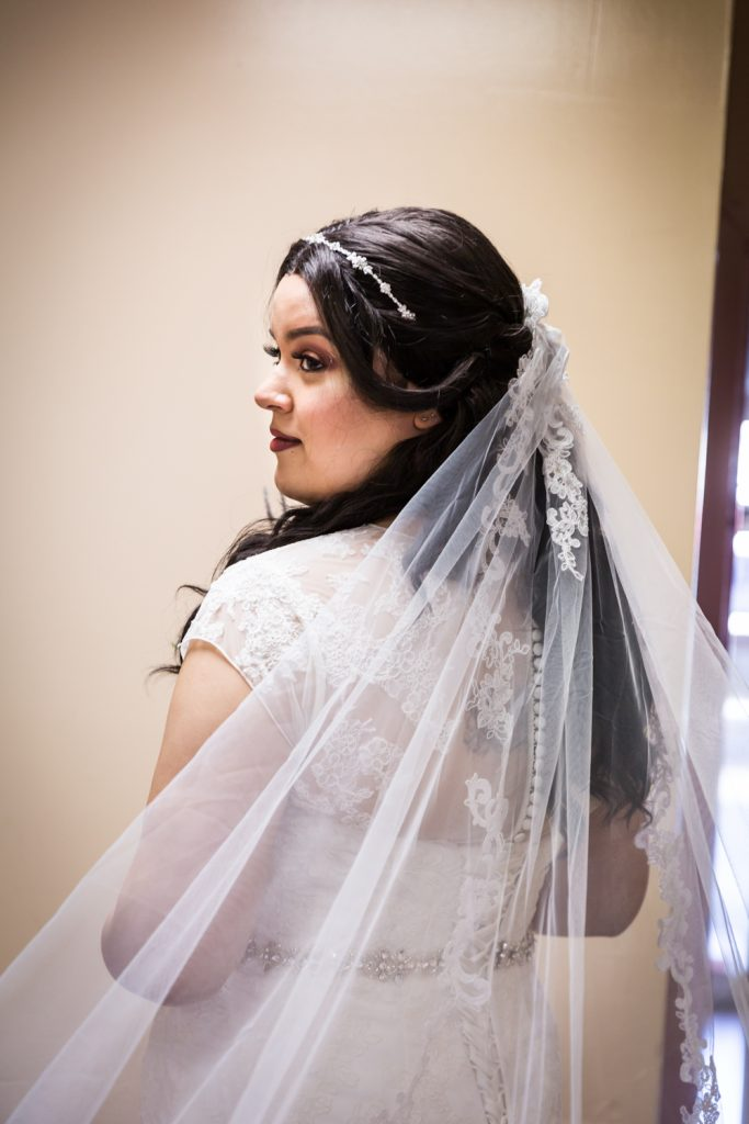 Portrait of bride looking over her shoulder for an article on wedding photography timeline tips