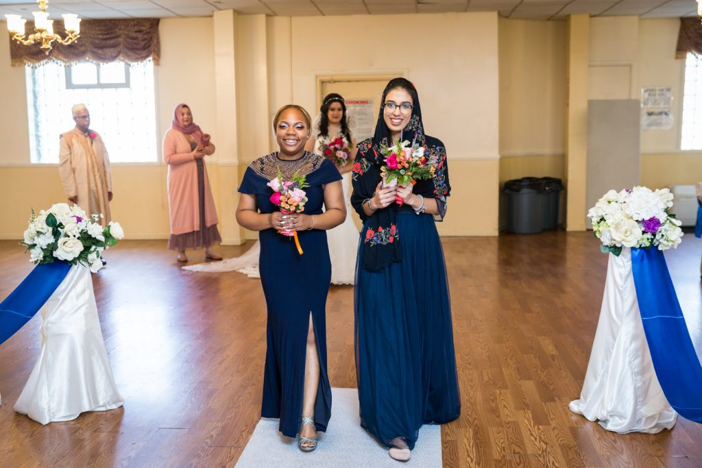 Two bridesmaids walking down aisle at Muslim wedding for an article on wedding photography timeline tips