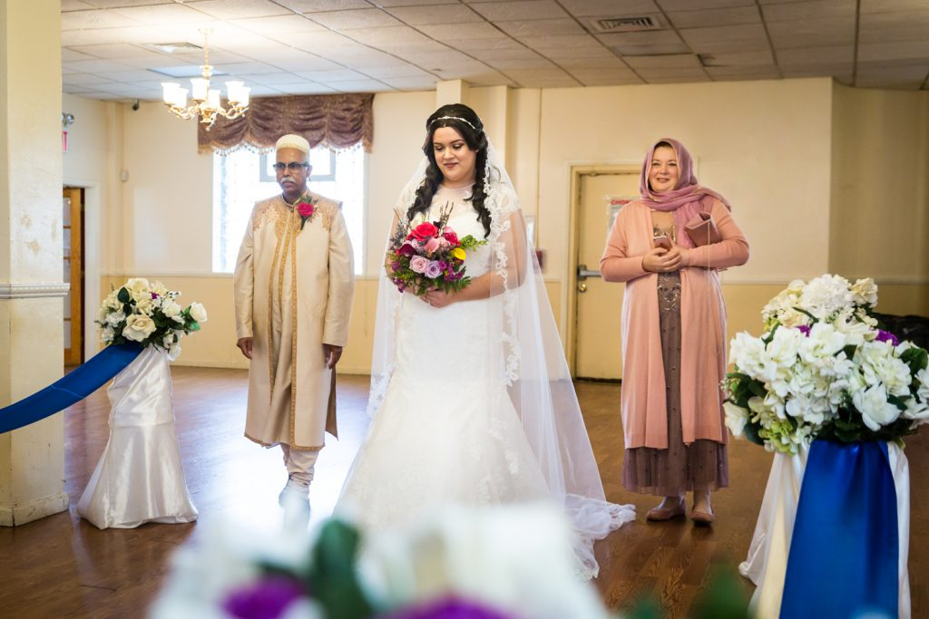 Bride and family walking down aisle for an article on wedding photography timeline tips