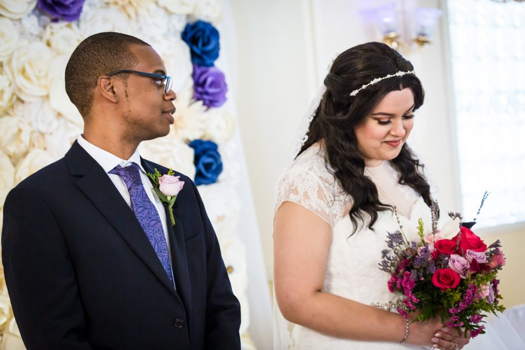 Groom looking at bride during ceremony for an article on wedding photography timeline tips
