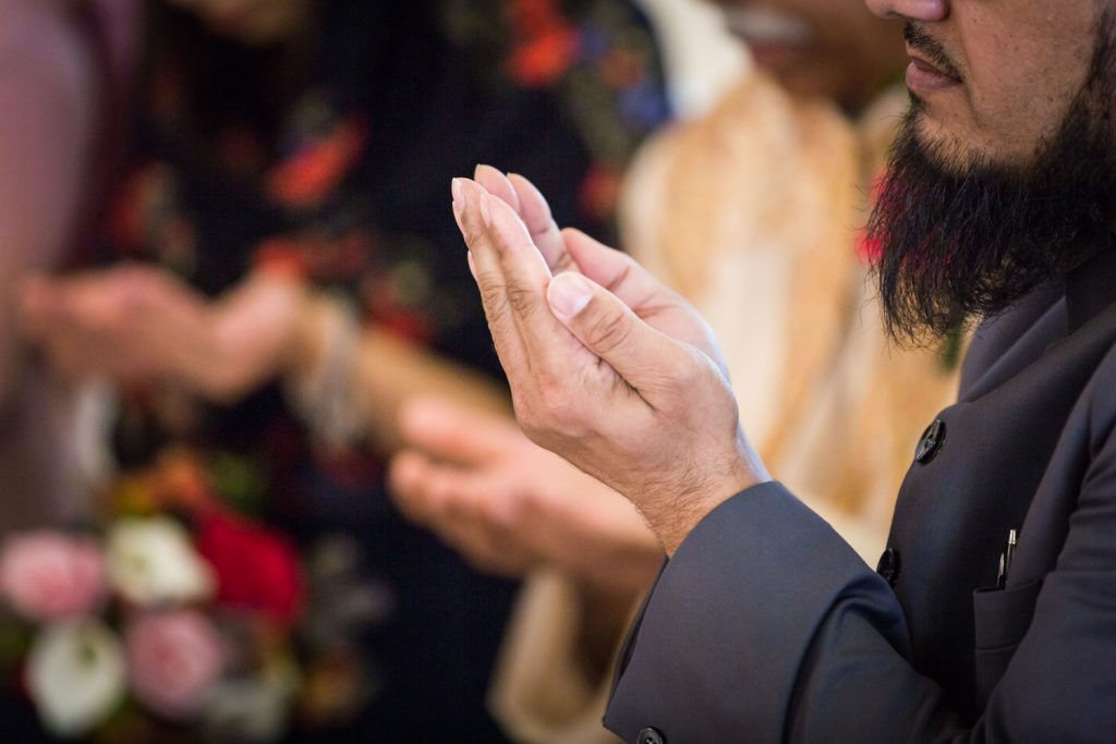Close up on an imam's hands during Muslim wedding ceremony
