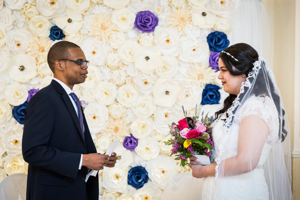 Bride and groom saying vows during wedding ceremony for an article on wedding photography timeline tips