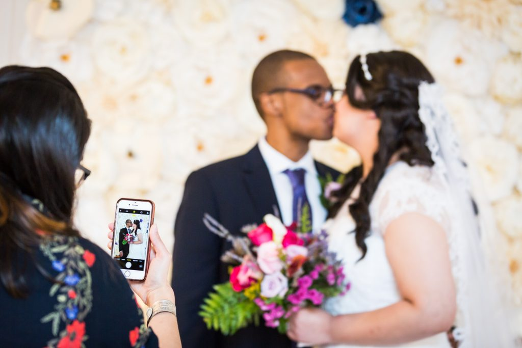 Guest taking photo with cell phone of bride and groom kissing