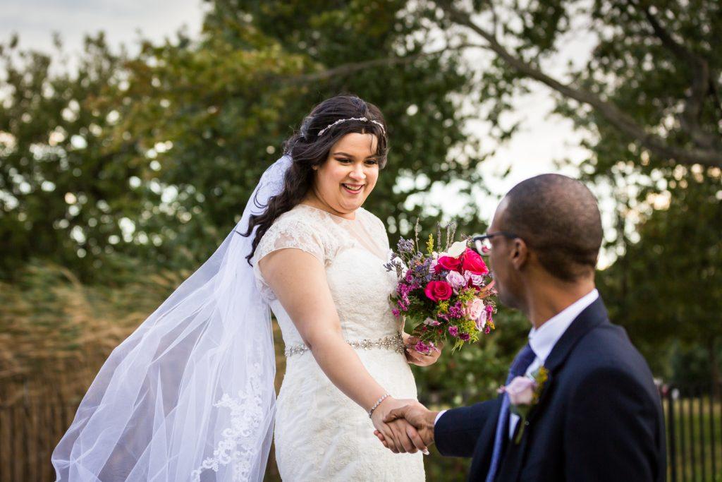 Groom taking bride's hand in park portrait