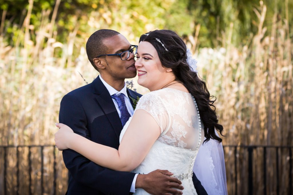 Bride and groom hugging in park for an article on wedding photography timeline tips