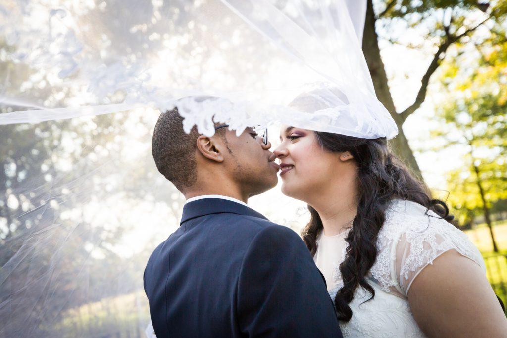 Bride and groom underneath blowing veil
