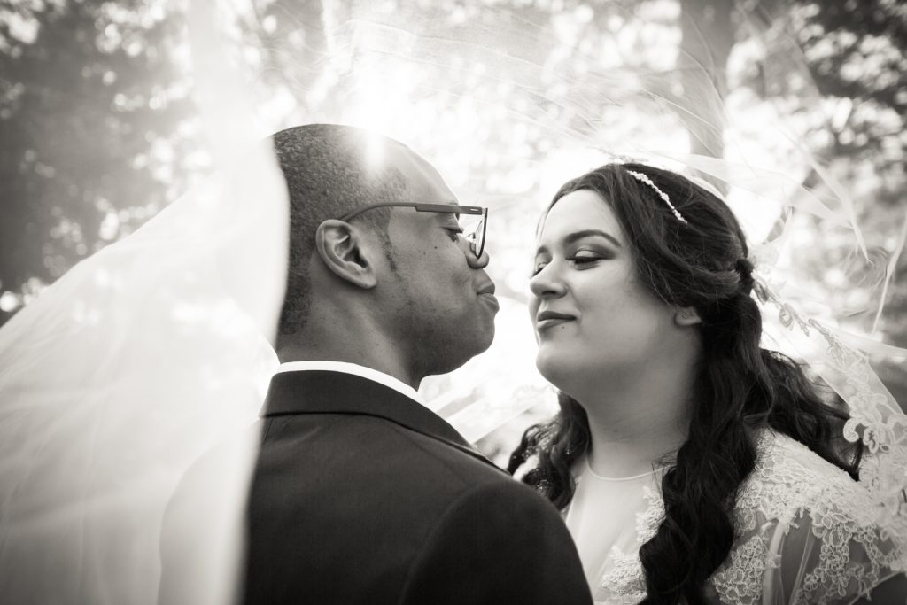 Black and white portrait of bride and groom under veil