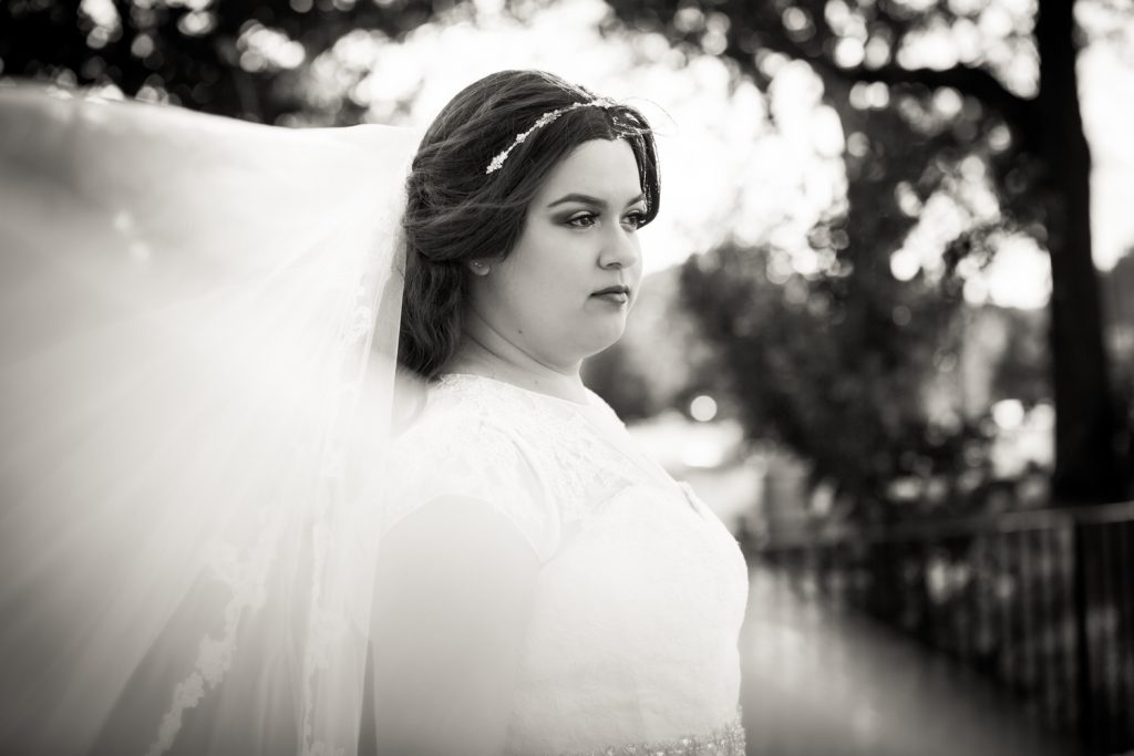 Black and white portrait of bride with blowing veil