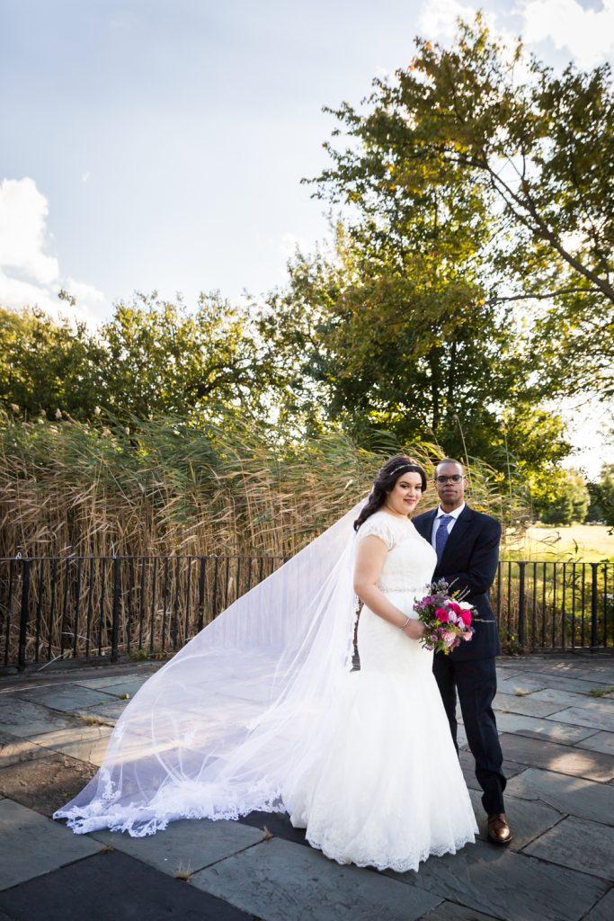 Portrait of bride with veil and groom in park