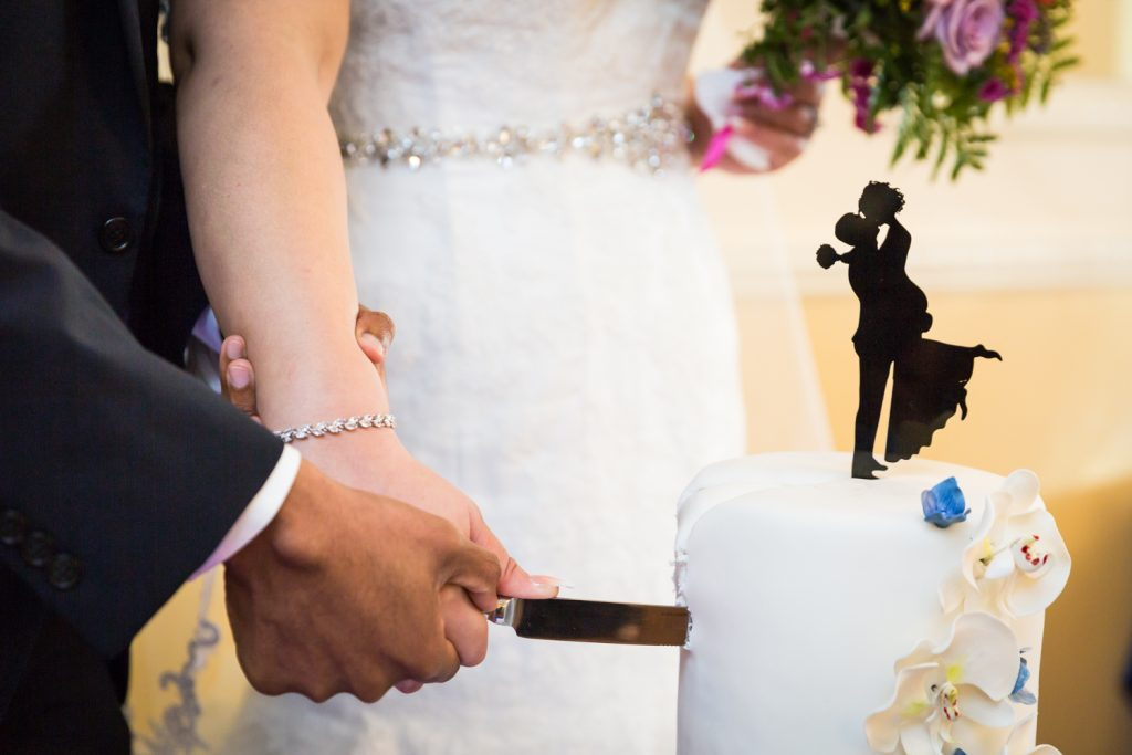 Close up on hands of bride and groom cutting cake