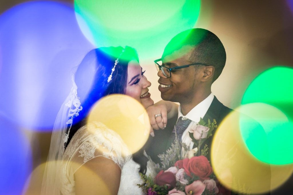 Portrait of bride and groom seen through colored lights