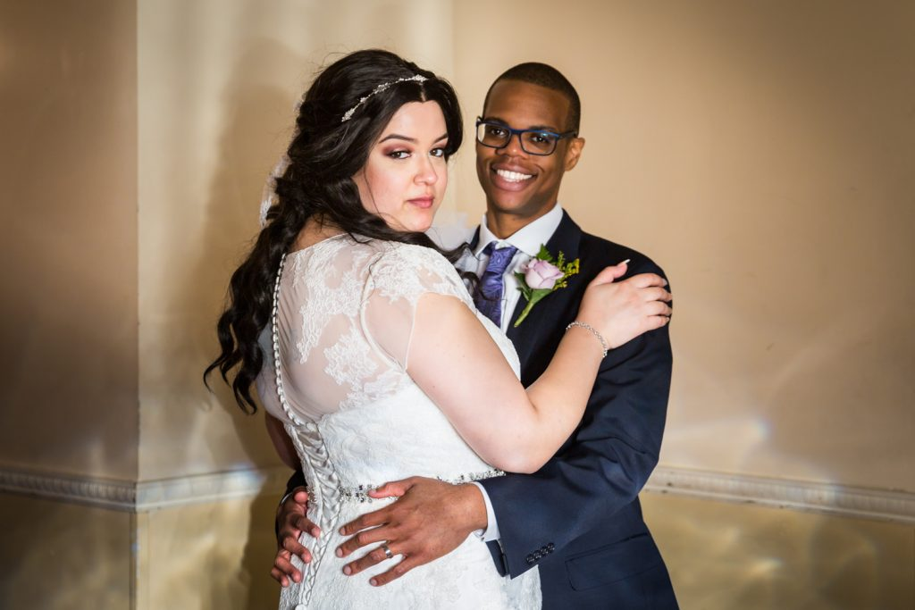 Portrait of bride looking over shoulder with groom