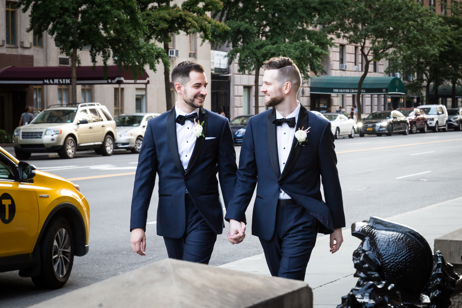 Two grooms walking down 72nd Street The Dakota apartment building
