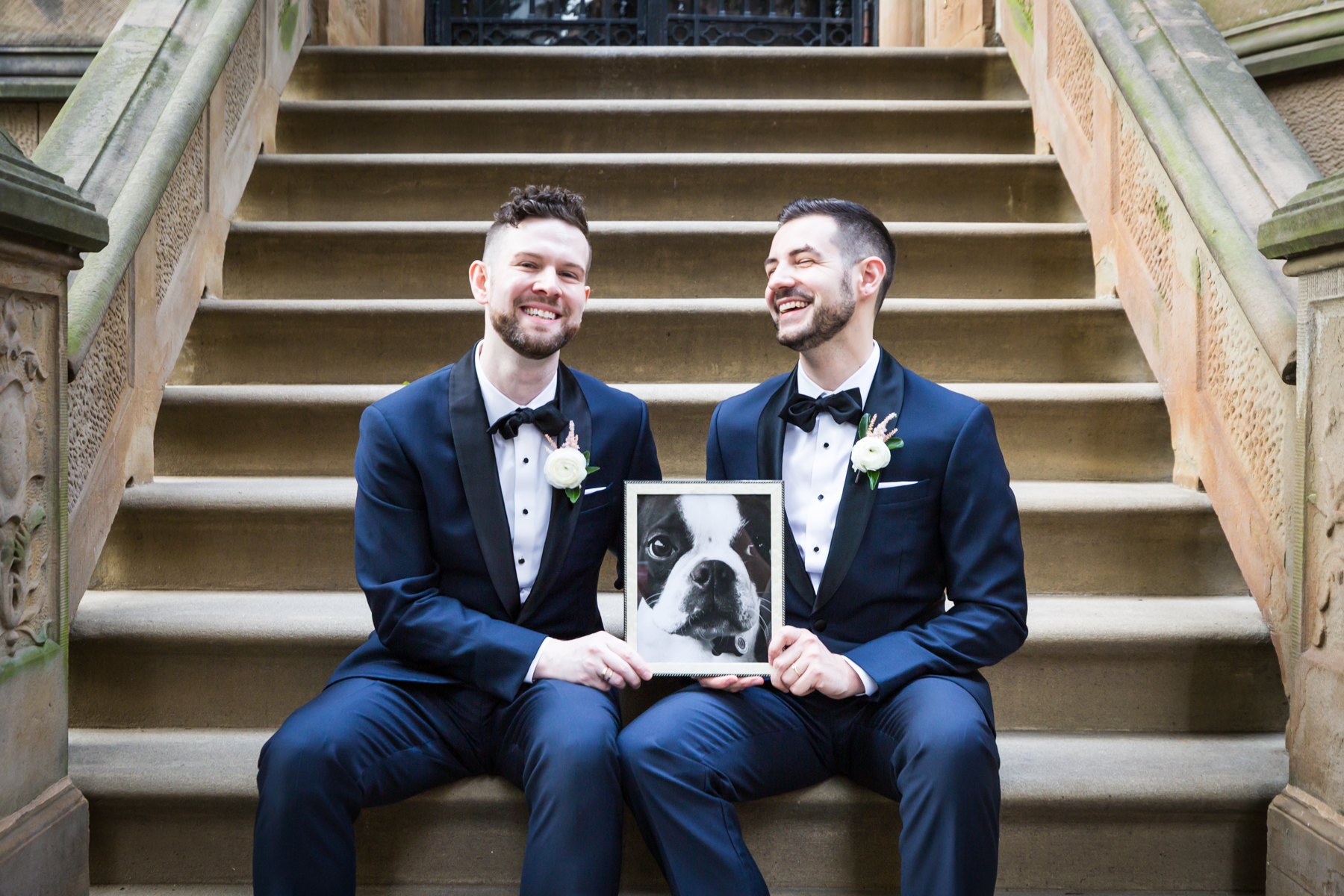 Two grooms sitting on brownstone stairs The Dakota apartment building