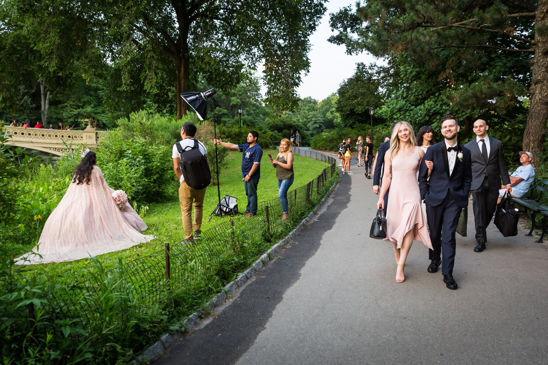 Wedding party walking past photo shoot for an article entitled, 'Do you need a permit to get married in Central Park?'