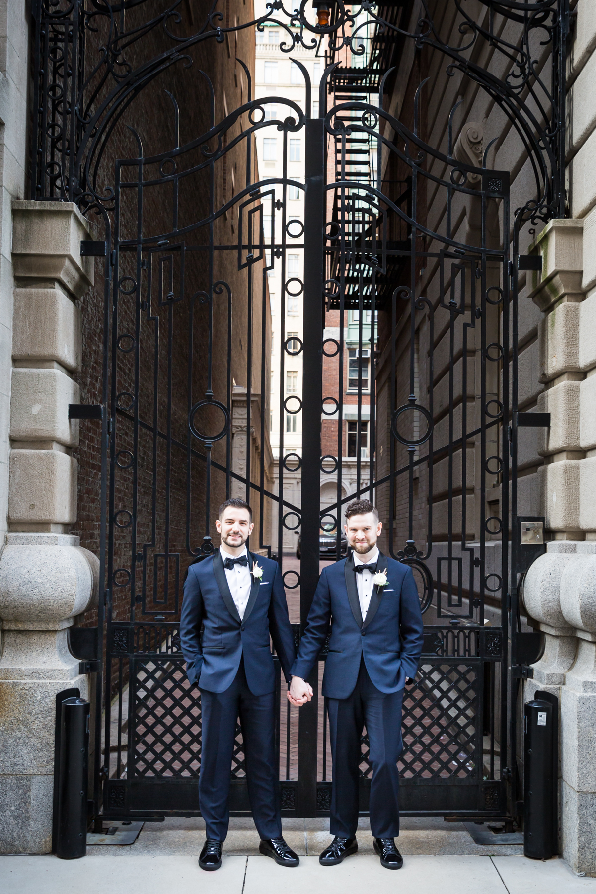 Two grooms in front of gate The Dakota apartment building