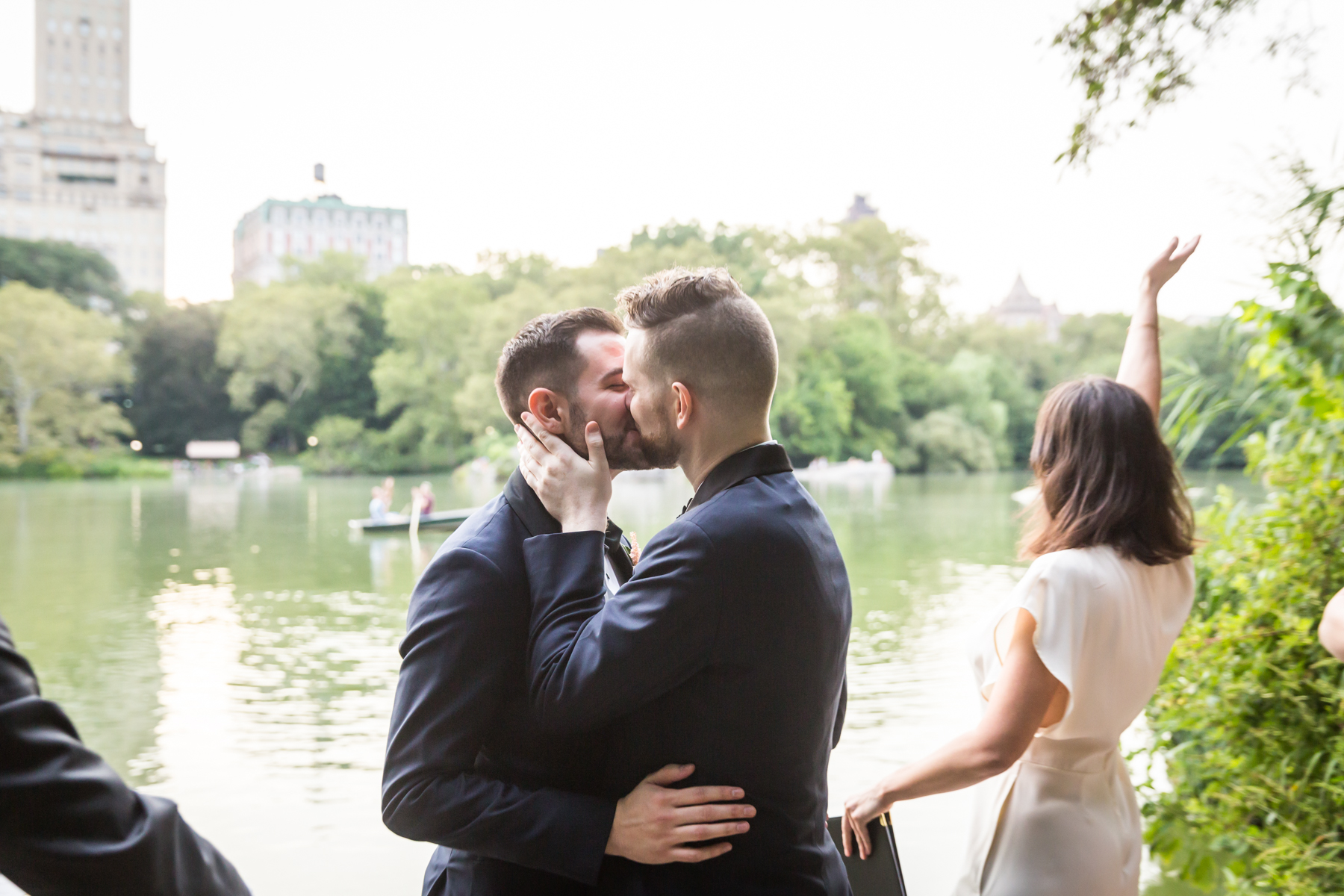 Two grooms kissing for an article entitled, 'Do you need a permit to get married in Central Park?'