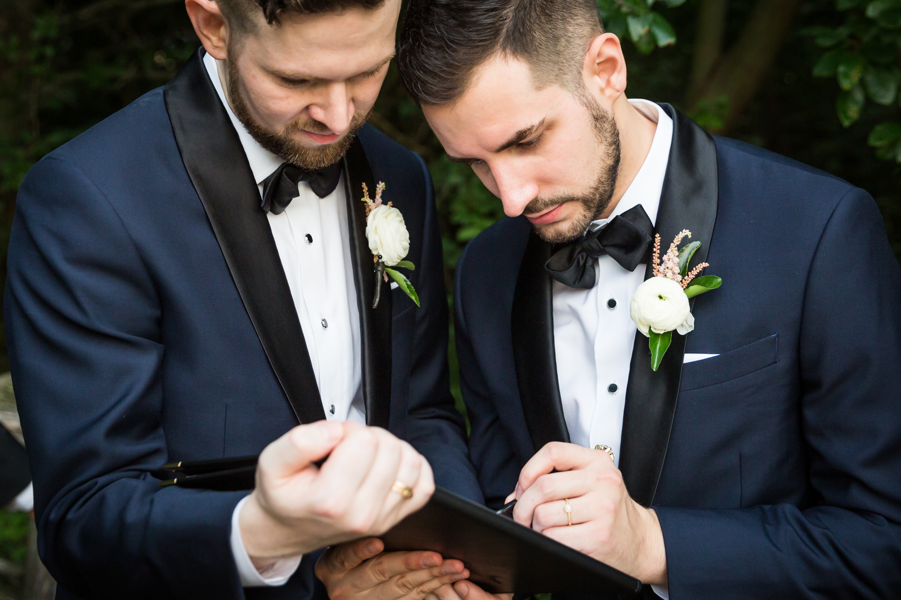 Two grooms signing marriage license for an article entitled, 'Do you need a permit to get married in Central Park?'