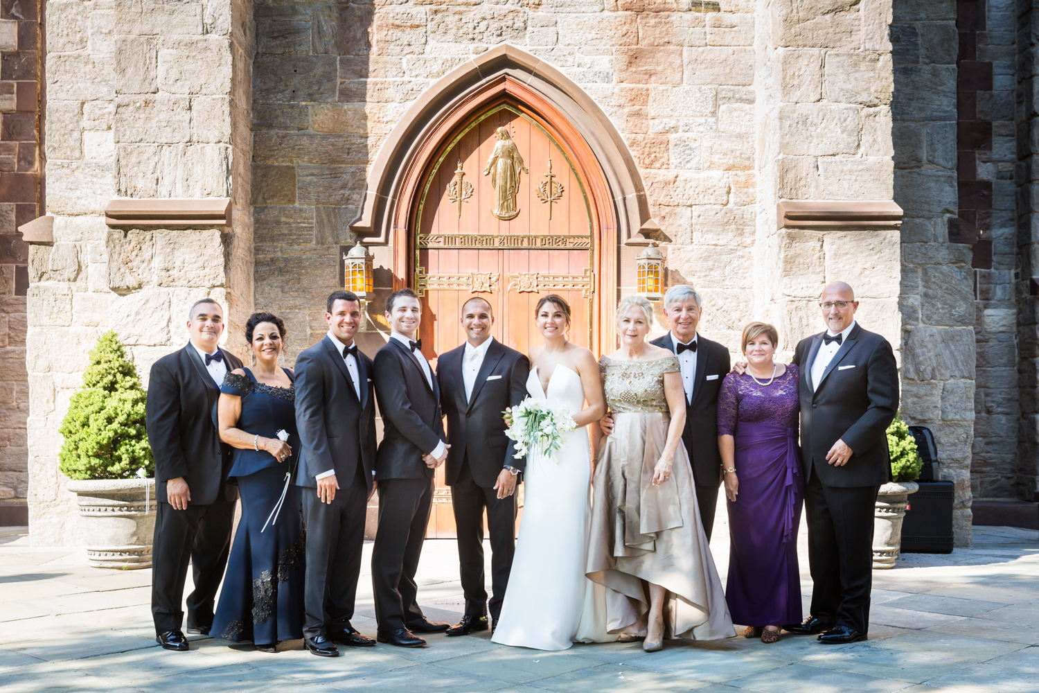 Family wedding portrait outside Fordham University Church for an article on Bronx Zoo wedding venue updates