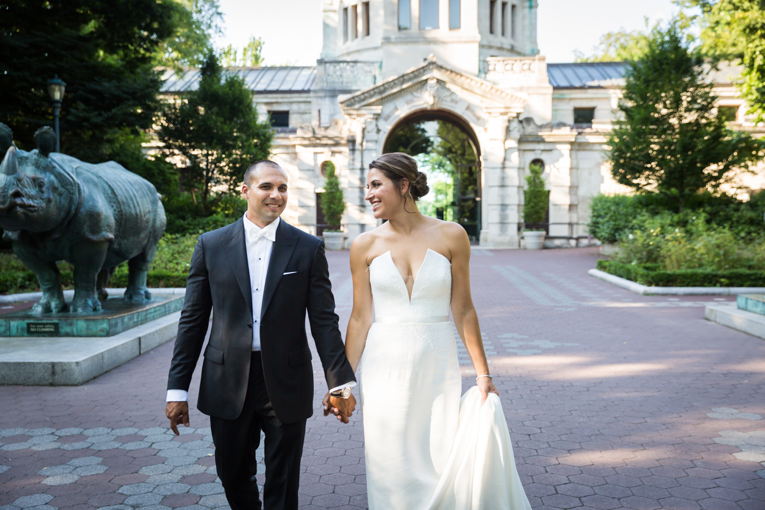 Bride and groom walking in front of Zoo Building for an article on Bronx Zoo wedding venue updates