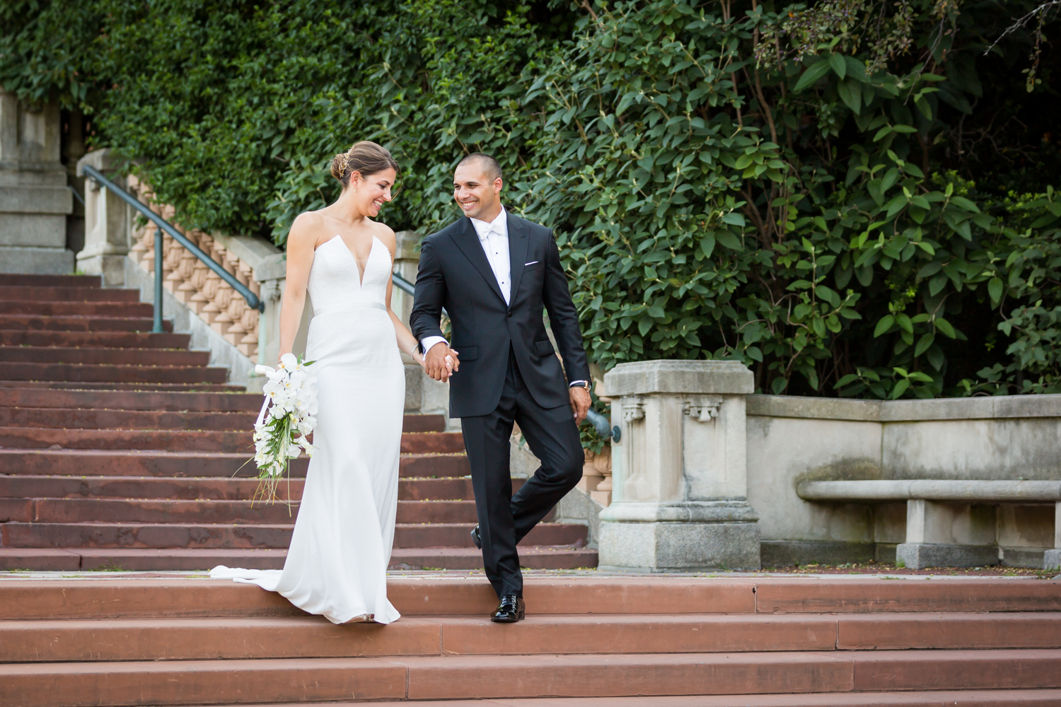 Bride and groom walking down Bronx Zoo entrance staircase for an article on Bronx Zoo wedding venue updates