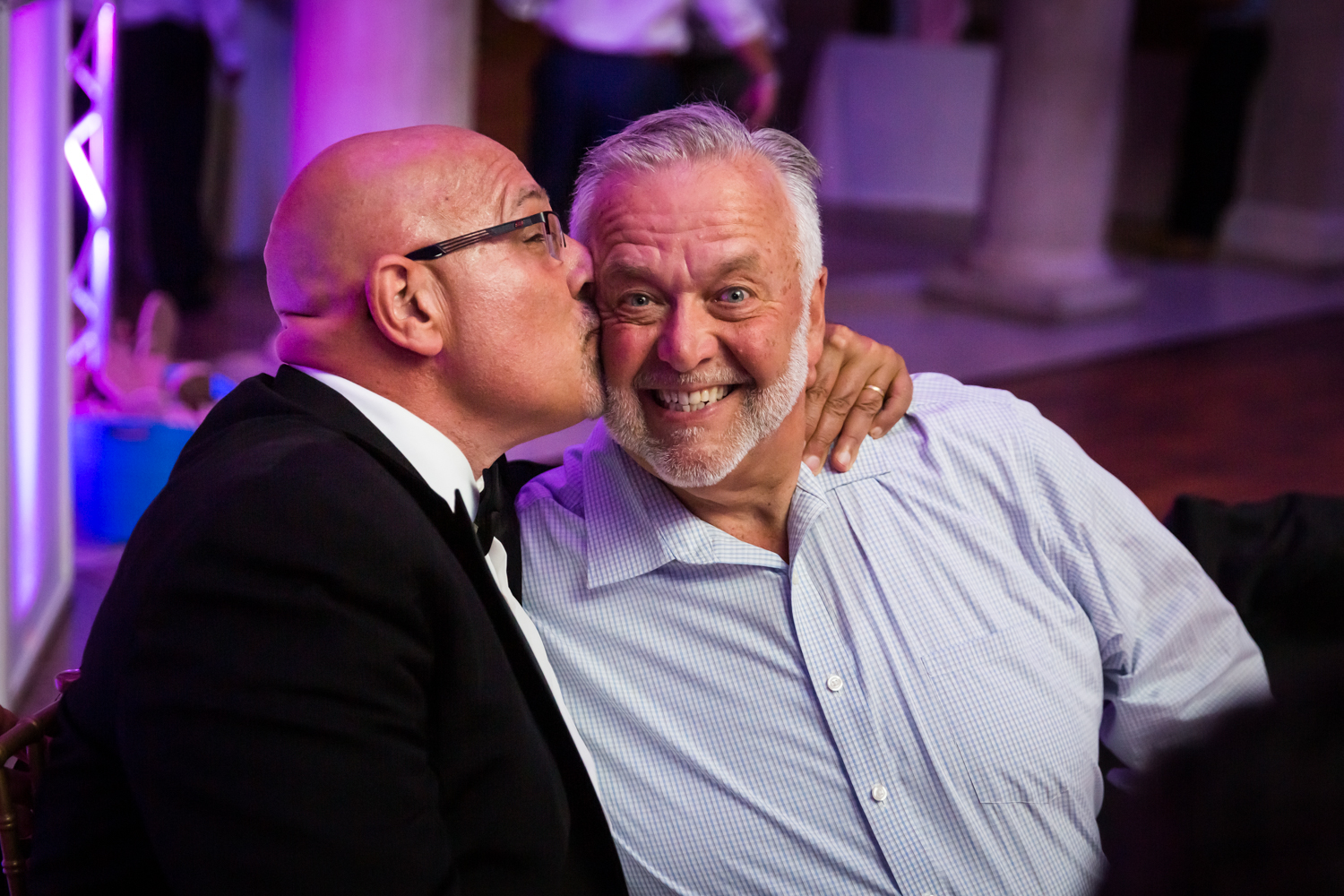 Father kissing guest on cheek for an article on Bronx Zoo wedding venue updates