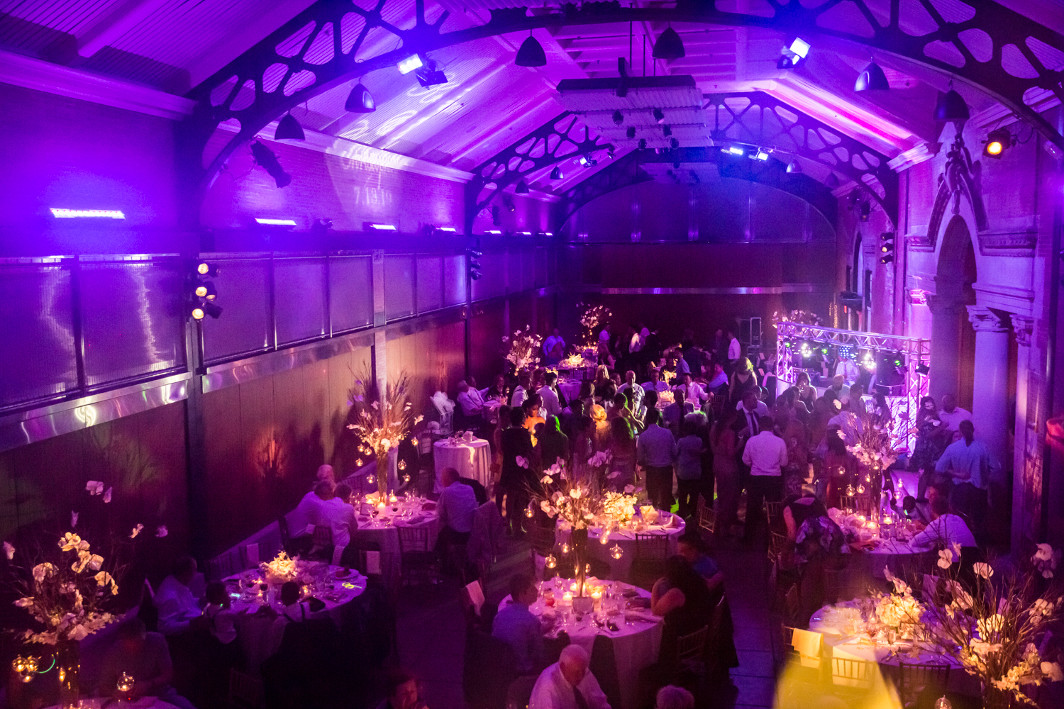 Reception tables with purple lighting for an article on Bronx Zoo wedding venue updates